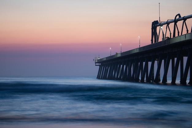 美しい夕焼け空の下の穏やかな海の近くの桟橋