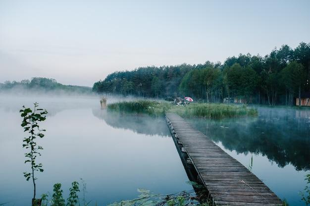 Пирс на озере возле леса