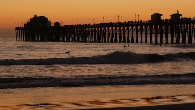 일몰, 캘리포니아 미국, 오션 사이드에서 부두 실루엣. 서핑 리조트, 바다 열대 해변. 파도를 기다리는 서퍼.