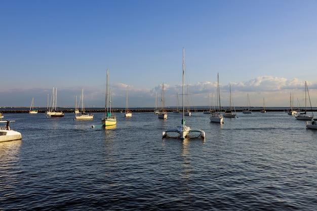 Пирс на скоростном катере с прекрасным видом на большую пристань для яхт с лодками в большой бухте.