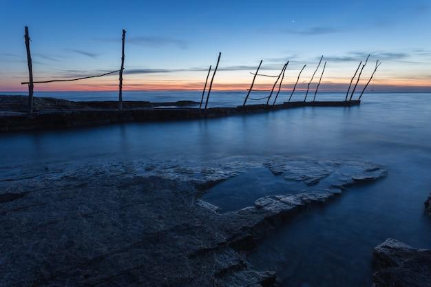 クロアチア、イストリア半島のsavudrijaのアドリア海の美しい夕日の下の桟橋