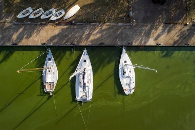 ボートのある桟橋、マリーナがたくさん。ドローンからの空中上面図。海藻による緑色の水