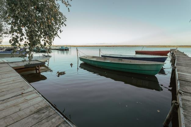 初秋の夕方に湖でボートのある桟橋。