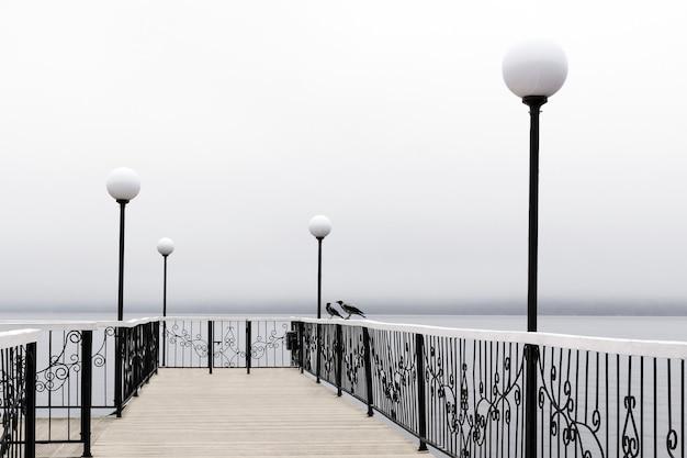 霧深い天候の湖に提灯があり、手すりに2羽のカラスが見える桟橋