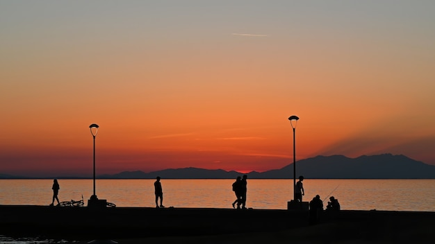 Pier with multiple fishing and walking people at sunset, parked bike, land  lampposts, greece