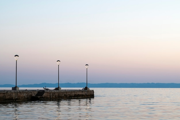 Pier with parked bike at sunset at aegean sea coast with land  lampposts in greece