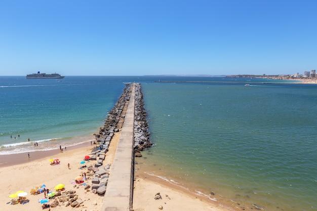 Pierce breakwater marina of the city of portimao. cruise ship in background.