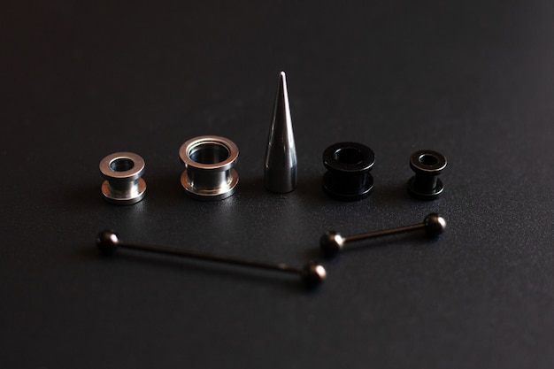 Piercing accessories on black close-up stainless metal jewelry for puncture lovers