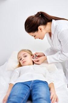 特別な装置を使用して白いローブの医者によって医療サロンで白人の子供の女の子に耳を突き刺します。美容と医学の概念