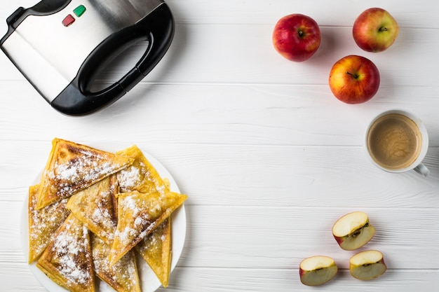 Pies lie on the table next to apples, a toaster and a cup of coffee
