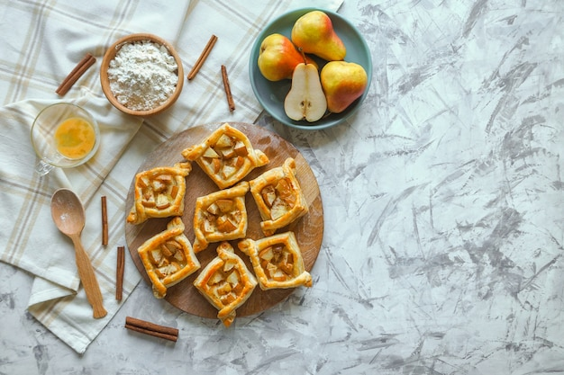 Pies of puff pastry with pears. homemade cake. the view from the top. mess on the table.