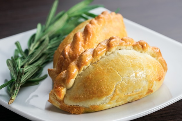 Pies with meat on a plate with a sprig of greenery