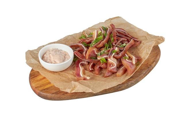 Свиные уши на тарелке, ресторанное блюдо, изображение изолировать