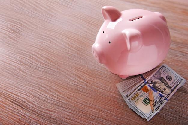 가벼운 표면에 돼지 moneybox 및 달러 지폐