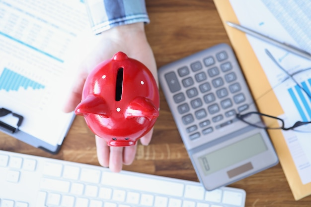 Pig piggy bank on female hand next to calculator and documents on table