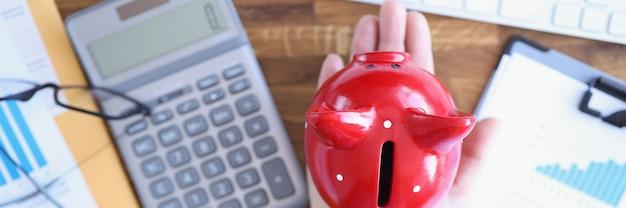 電卓の横にある女性の手にある豚の貯金箱と中小規模のテーブルのドキュメント