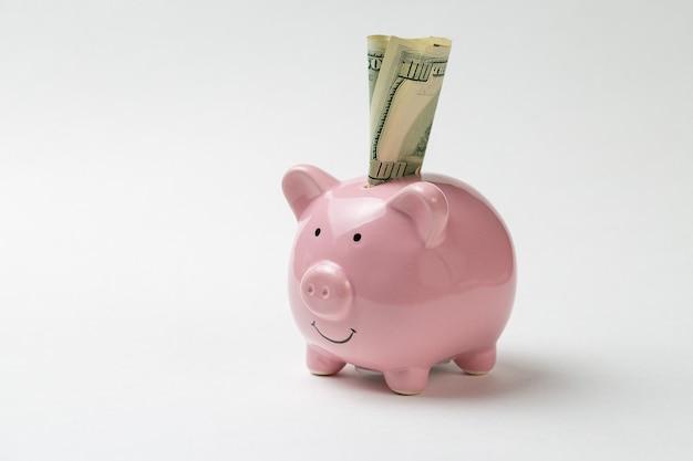 100달러 지폐와 비트코인의 실물 동전 배경에 있는 돼지 저금통