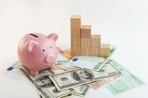 豚の形をした貯金箱、成長するグラフの木製の立方体、ユーロ紙幣、孤立した白い背景の米ドル