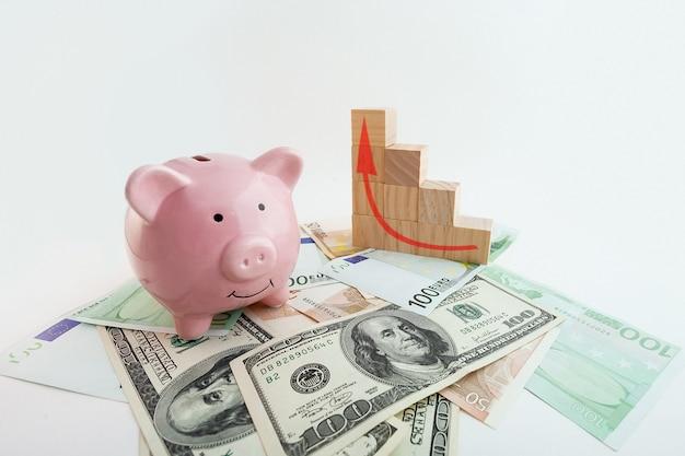 豚の形をした貯金箱、成長するグラフの木製キューブ、ユーロ紙幣、米ドル