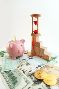 Pig shaped piggy bank, hourglass, bitcoin coins, growing graph wood cubes, euro banknotes and us dollars on isolated white background