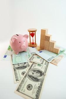 豚の形をした貯金箱、砂時計、成長するグラフの木製キューブ、ユーロ紙幣、米ドル