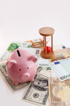 Pig shaped piggy bank, hourglass, growing graph wood cubes, euro banknotes and us dollars on isolated white background
