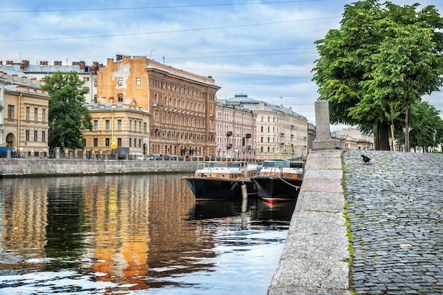 Голубь на набережной реки фонтанки в санкт-петербурге, домики на набережной и прогулочные лодки на воде.