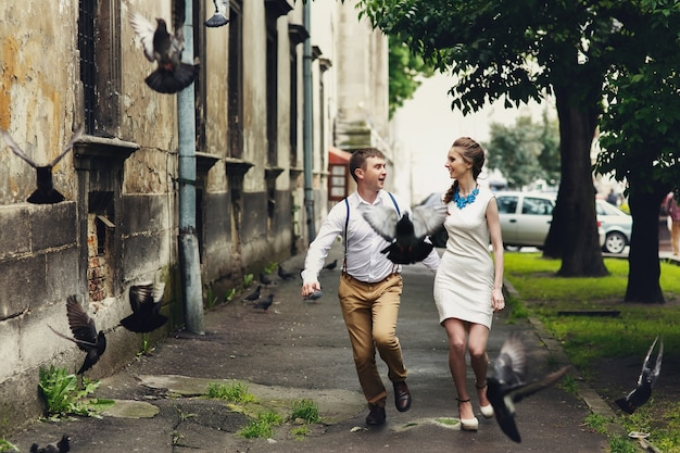 Pigeons fly before happy couple running outside
