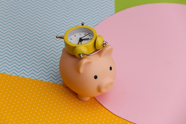 Piggy bank and alarm clock on creative colorful paper background. time to invest
