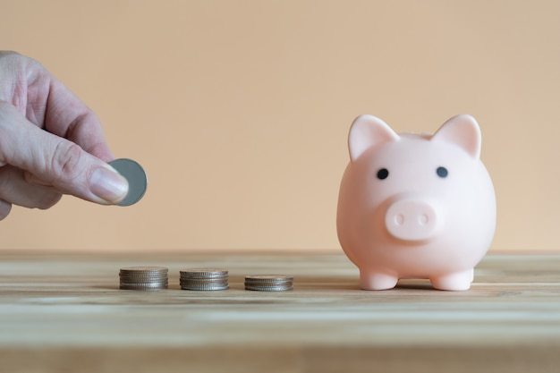 돼지 저금통과 밝은 주황색 배경의 나무 테이블에 놓인 동전 더미를 줍는 손