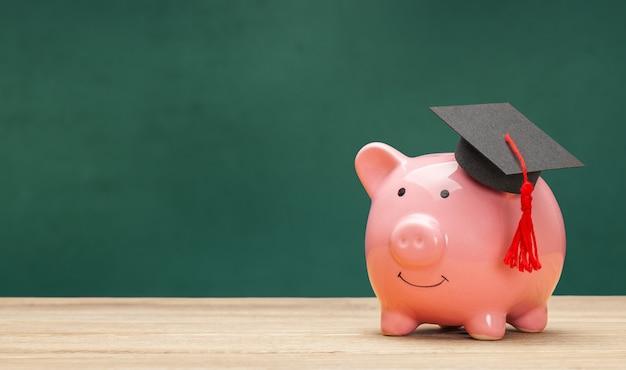 Копилка и черная шляпа выпускника, изолированные на белом фоне. фон зеленый школьный совет