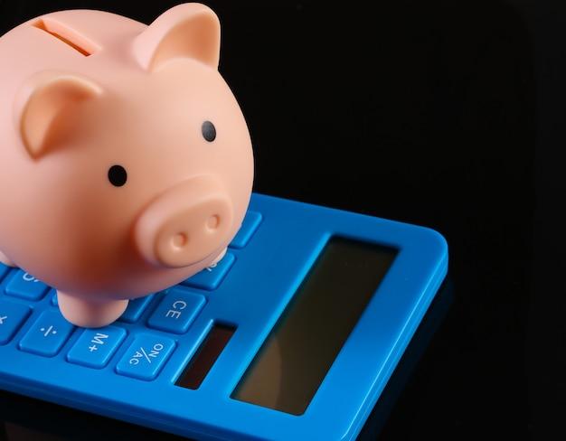 黒い表面に分離された貯金箱と電卓