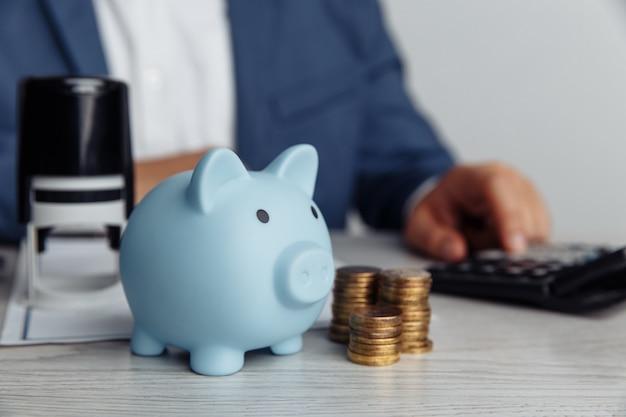 Копилка и монеты на столе в офисе. экономьте деньги и финансовую концепцию управления