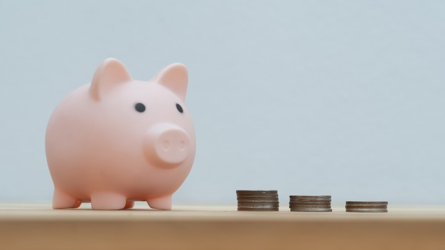 연한 파란색 배경의 나무 탁자에 놓인 돼지 저금통과 동전 더미