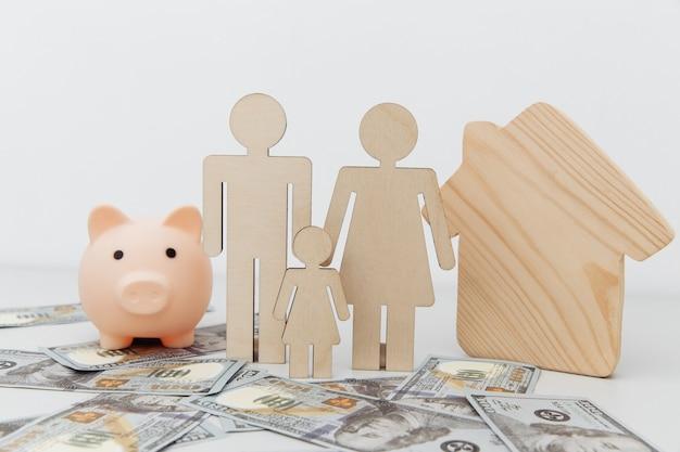 Копилка и фигуры семьи с деревянным домом на долларовых банкнотах