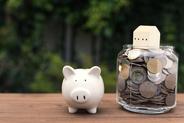 Копилка и модель дома на деньги, монеты, стеклянная банка, на деревянном столе, концепция сбережений и инвестиций