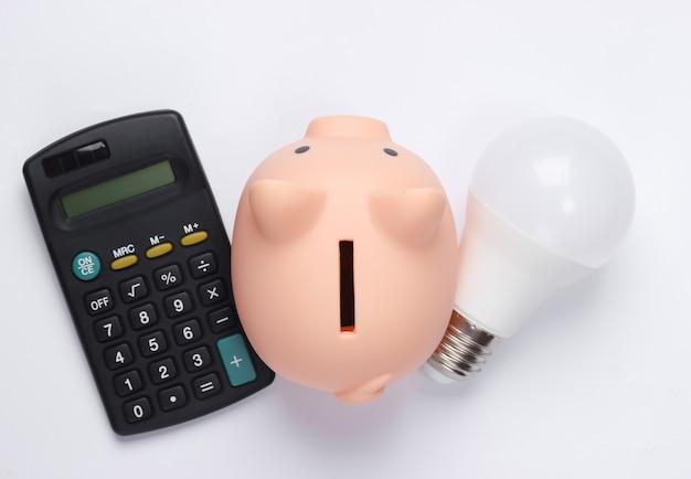 Копилка и светодиодная лампочка, калькулятор на белом. сохранение энергии.
