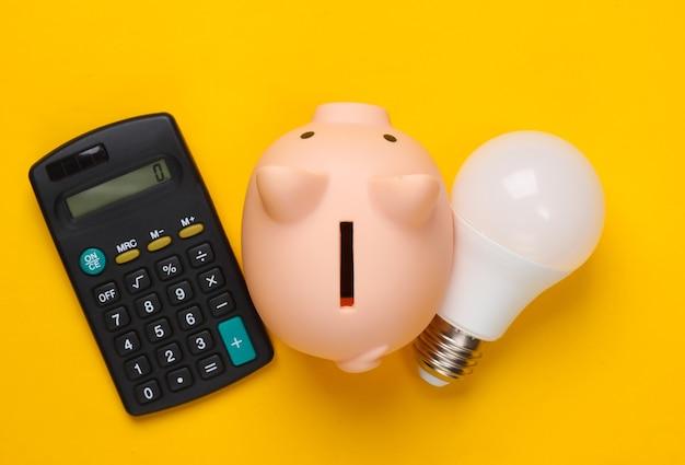 Копилка и светодиодная лампочка, калькулятор на желтом. сохранение энергии