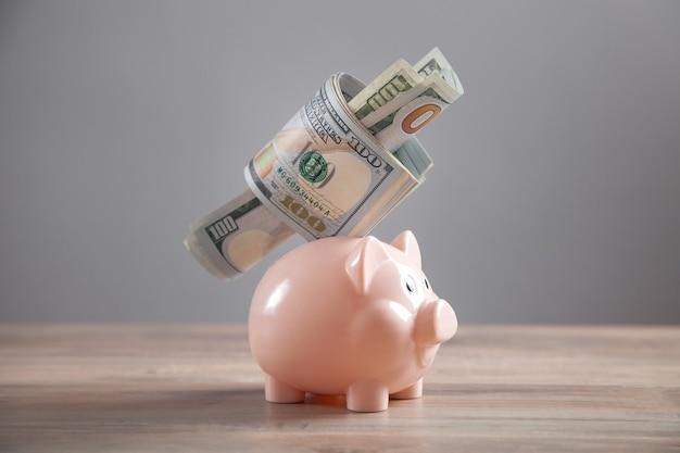 貯金箱と机の上のお金。保存します。ビジネス