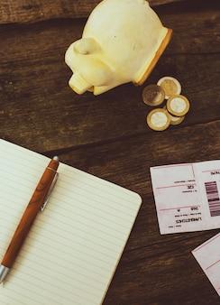 貯金箱と木製のテーブルのメモ帳