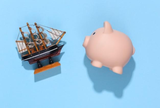 Копилка и корабль на синем солнечном ярком. планирование путешествия.
