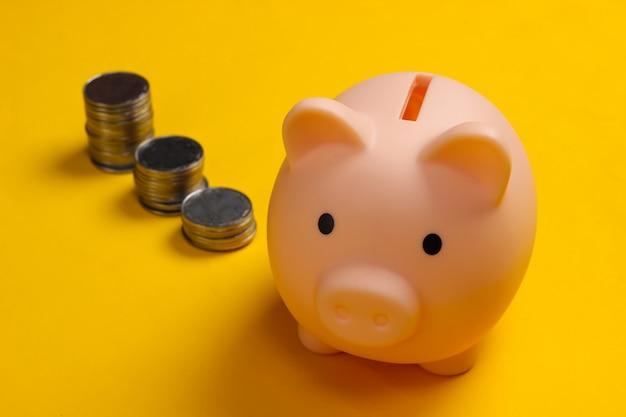 貯金箱と黄色い表面のコインのスタック、投資のためのお金、富、財政を節約します