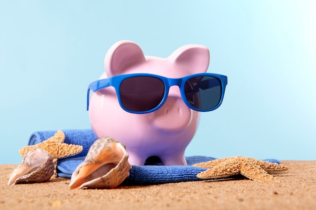 Piggy bank on a beach with sunglasses