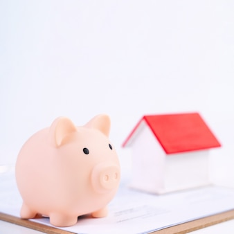 Копилка, красивая модель деревянного дома над подписанным контрактом на белом фоне, концепция экономии денег, чтобы купить страхование жилья, крупным планом, копией пространства.