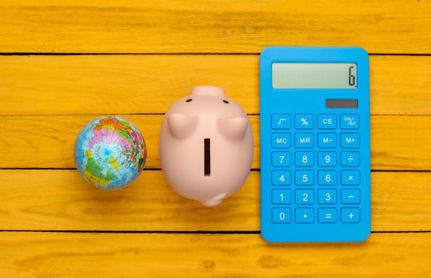 Piggy bank and blue calculator, globe on a yellow wooden surface. travel or eco concept. top view
