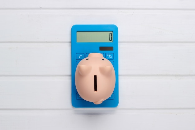 Piggy bank and blue calculator on white wooden surface. top view