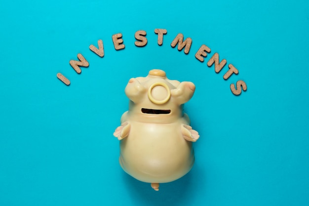 Piggy bank on blue surface with text investments with letters minimalistic business concept