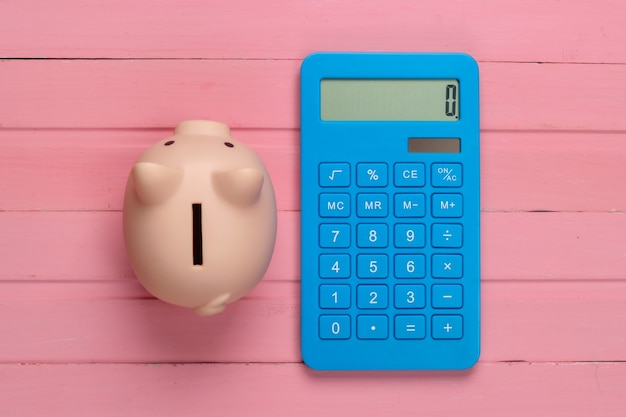 Piggy bank and calcuator on pink wooden surface. top view