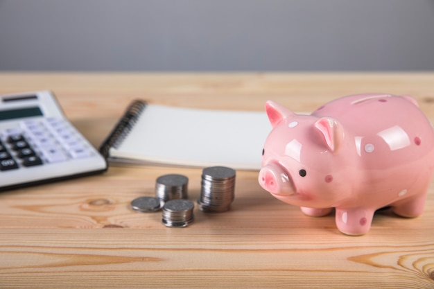 貯金箱、電卓、木の表面のコイン