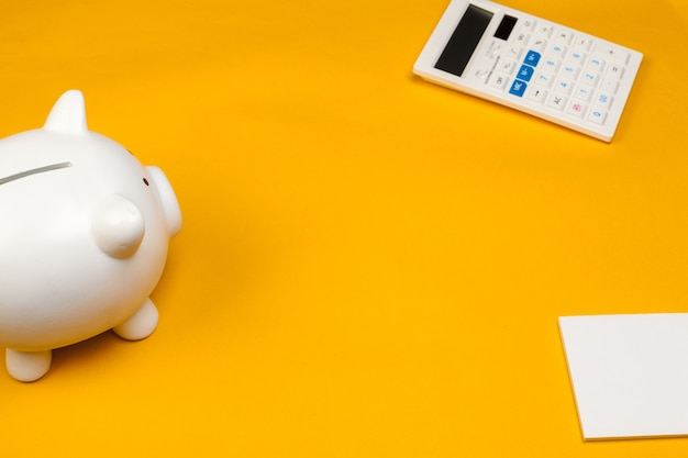 Piggy bank and calculator on yellow background